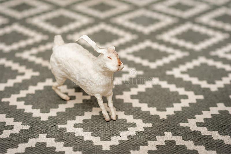 Wit konijntje op een weefselachtergrond van een tapijt met een geometrisch patroon Pasen-concept, tederheid, uniciteit, schoonhei stock foto