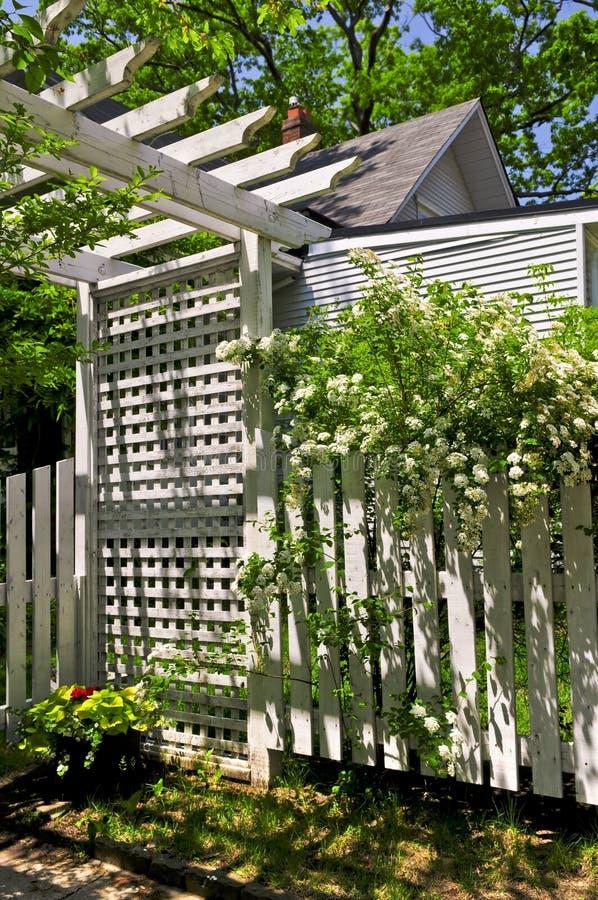Wit latwerk in een tuin stock afbeelding