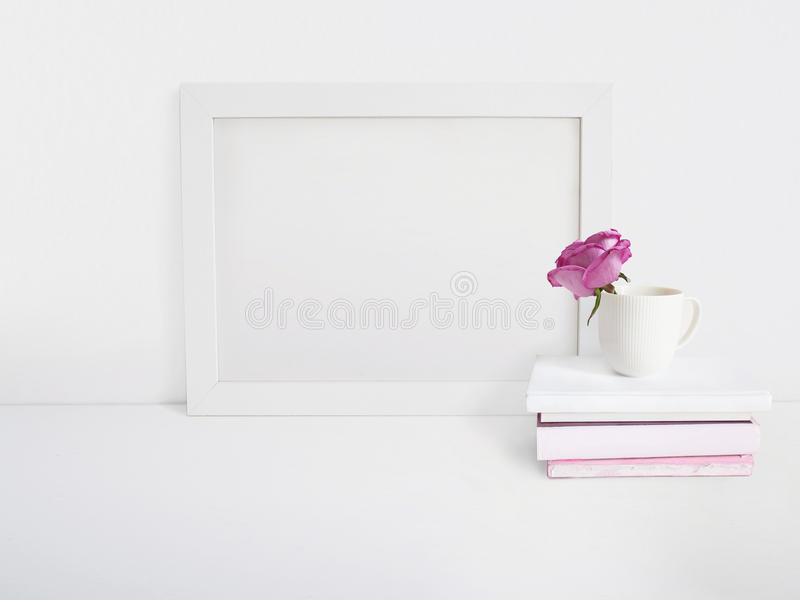 Wit leeg houten kadermodel met een roze bloem in een porseleinkop en een stapel van boeken die op de lijst liggen affiche stock foto
