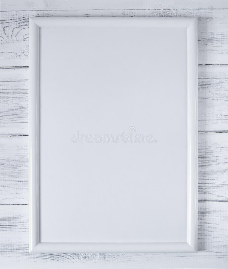Wit leeg kader op de achtergrond van witte houten raad royalty-vrije stock afbeelding