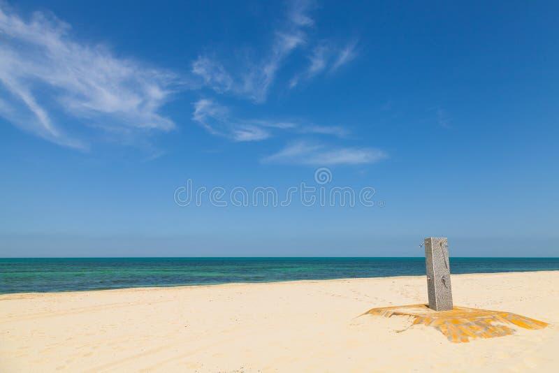 Wit leeg zandig strand met douche stock foto's