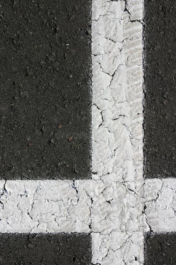 Wit loodlijn gestalte gegeven kruis op zwart asfalt royalty-vrije stock afbeelding
