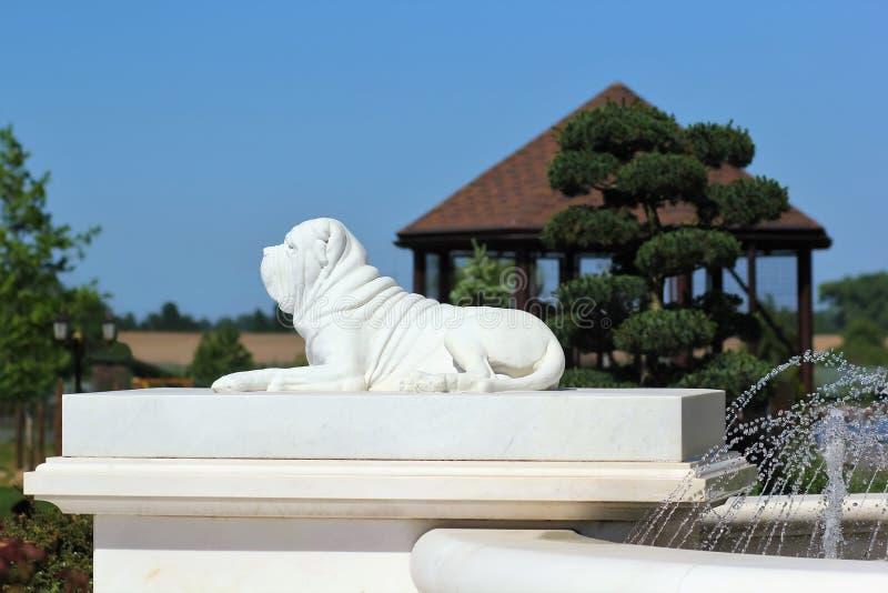 Wit marmeren standbeeld van een het leggen hond, profielmening, landschapsdecoratie royalty-vrije stock foto