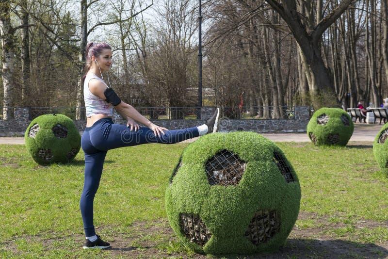1 wit meisje in een bovenkledij leidt in openlucht in het Park op, meisje die het uitrekken zich voet naast de futbolny bal doen royalty-vrije stock foto's