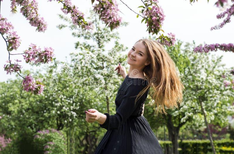 1 wit meisje met lang haar in een zwarte kleding die in een bloeiende Apple-boomgaard, meisje het glimlachen spinnen royalty-vrije stock foto's