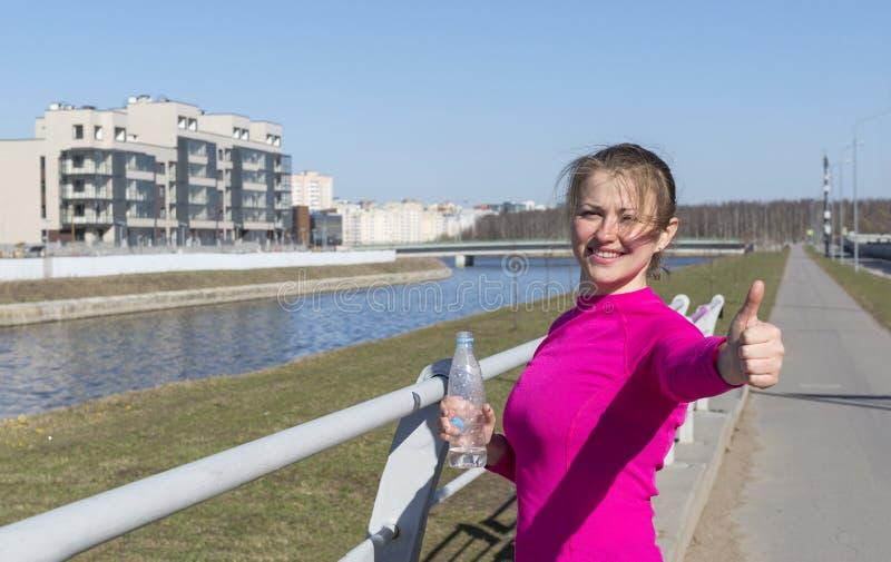1 wit meisje in roze sportenbovenkant met een fles water aan haar hand toont in openlucht tekenklasse, jonge vrouw op het kanaal royalty-vrije stock foto