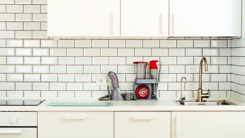 Wit minimalistic keukenbinnenland en ontwerp De achtergrond van de tegelmuur Huishoudapparaten - mixer, vacuümmachine stock afbeeldingen