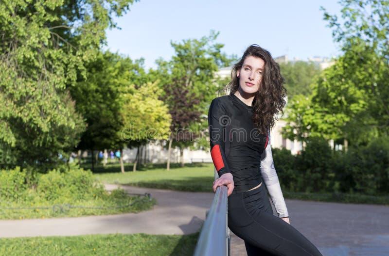 1 wit mooi slank donkerbruin meisje met lang golvend haar in sportkledingstribunes tegen de bomen royalty-vrije stock fotografie