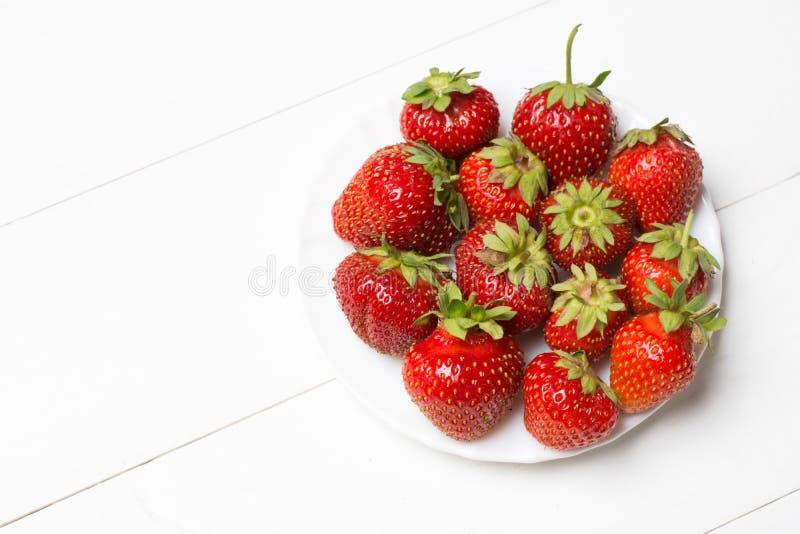 Wit plaathoogtepunt van aardbeien op lijst royalty-vrije stock afbeeldingen