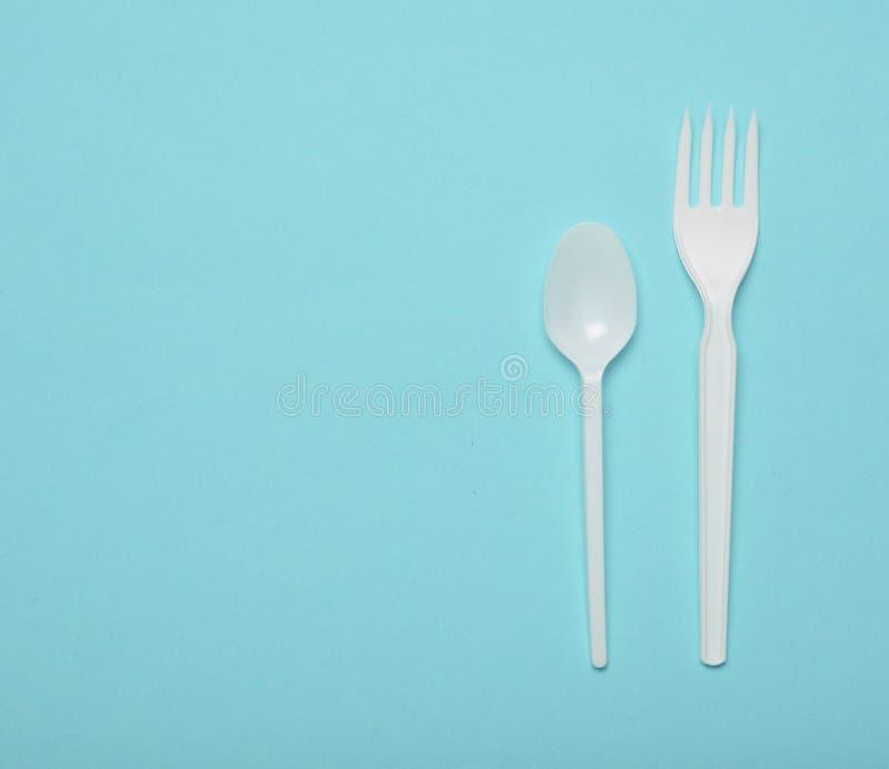 Wit plastic bestek voor picknicks op een blauwe achtergrond Beschikbare lepel, vork Hoogste mening, exemplaarruimte stock afbeelding