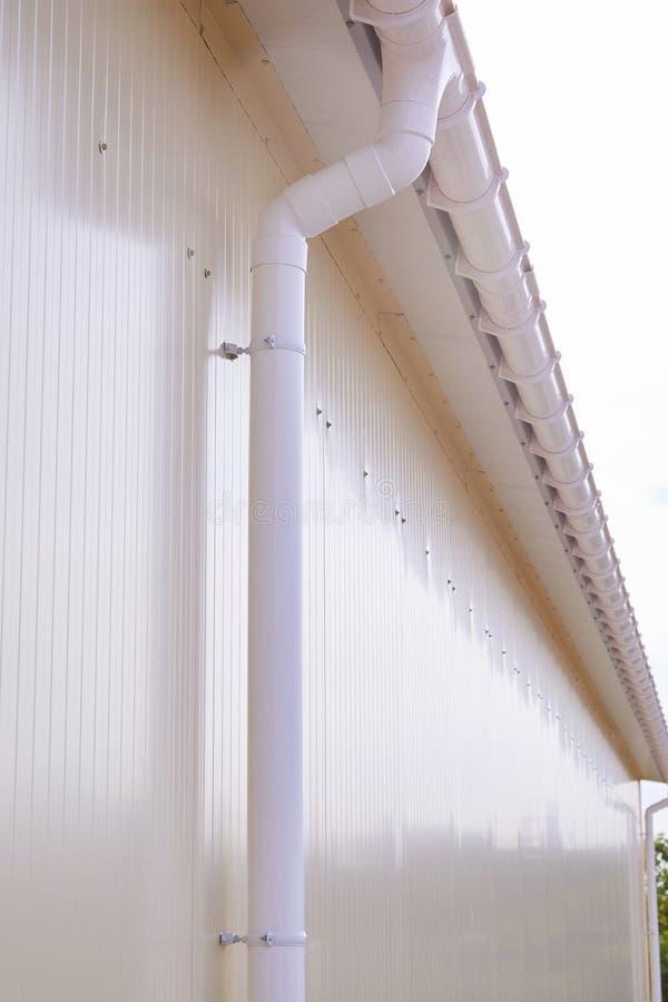 Wit plastic regen guttering systeem De pijpbuitenkant van de Gutteringsdrainage stock foto