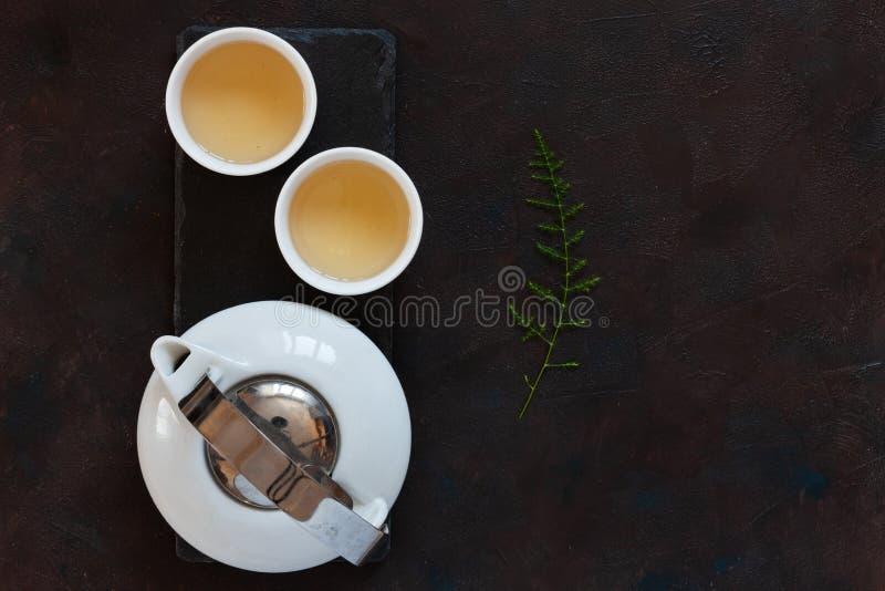Wit porselein Aziatisch theestel met groene theemelk Oolong op zwart steenbureau Sluit omhoog, hoogste mening stock fotografie