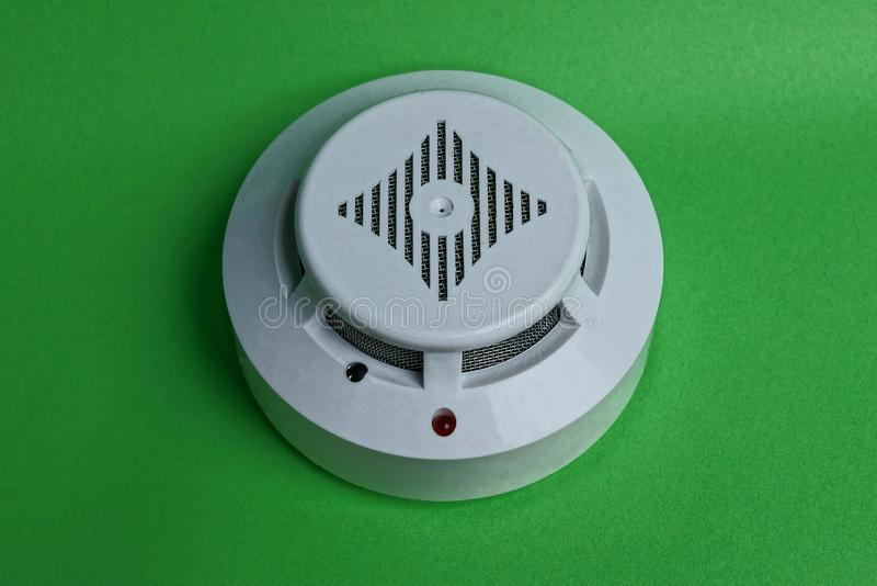 Wit rond plastic brandalarmapparaat op de groene muur stock afbeeldingen