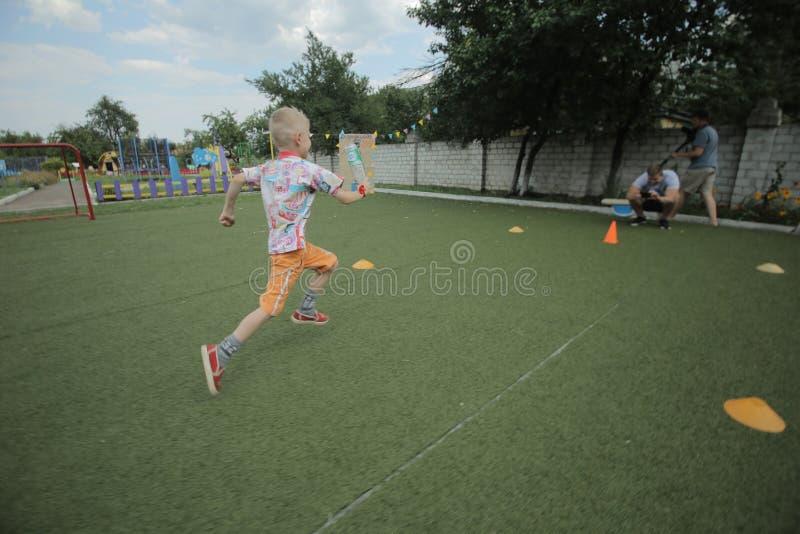 Wit-Rusland, Bobruisk - juni 20, 2018: Weinig jongen die rond de speelplaats lopen Kunstmatig gras royalty-vrije stock afbeelding
