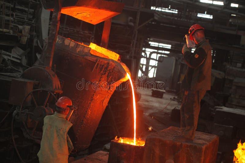 Wit-Rusland, Minsk, 2014 Het werk in de gieterij gesmolten metaalarbeider bij een metallurgische installatie stock foto's