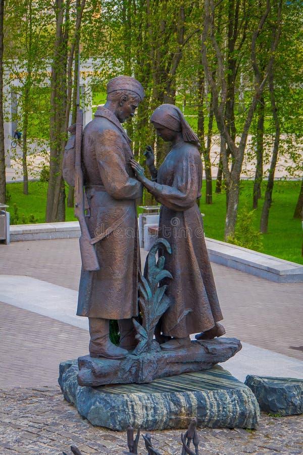 WIT-RUSLAND, MINSK - MEI 01, 2018: De openluchtmening van bronsbeeldhouwwerk van de mens en vrouw in Victory Park bij schemering  stock afbeeldingen
