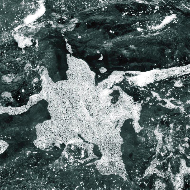 Wit schuim op de oppervlakte van glashelder zeewater stock afbeelding