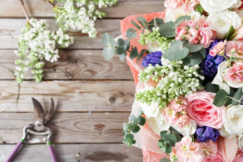 Wit sering en mengelingsbloemenboeket op houten achtergrond oude rustieke lijst, een rol van streng en ozhnitsy tuin bovenkant stock foto