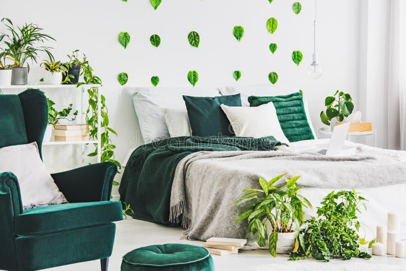 Wit slaapkamerbinnenland met het bed van de koningsgrootte met het grijze smaragdgroene beddegoed van Nd, stedelijke wildernis en stock foto's