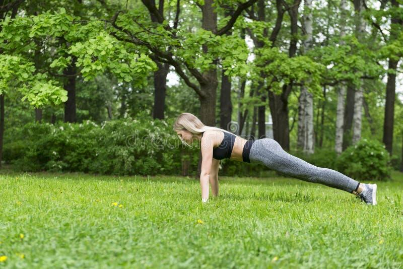 1 wit slank blondemeisje met lang haar die sporten in het Park onder de bomen doen stock fotografie