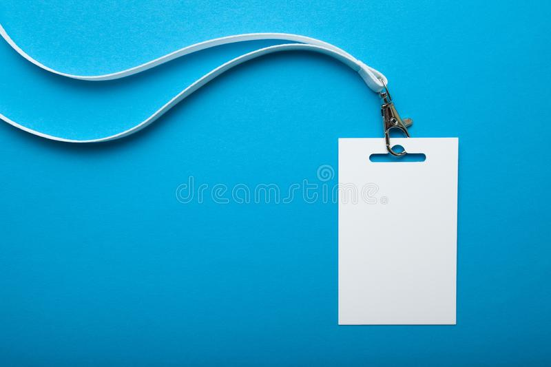 Wit sleutelkoord en plastic kenteken met lege ruimtespot die omhoog op blauwe achtergrond wordt geïsoleerd stock foto