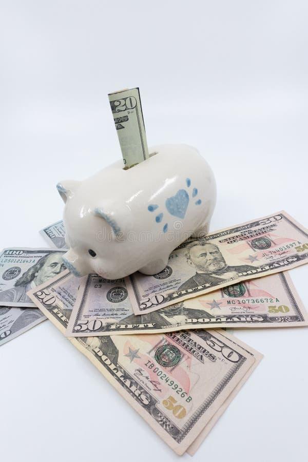 Wit spaarvarken op een stapel van de munt van Verenigde Staten tegen een witte achtergrond royalty-vrije stock afbeelding
