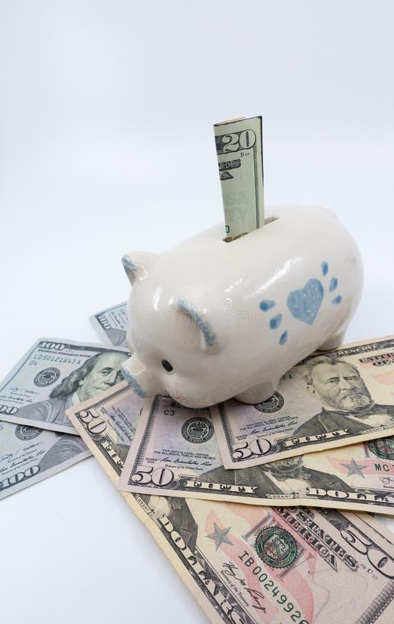 Wit spaarvarken op een stapel van de munt van Verenigde Staten tegen een witte achtergrond stock afbeelding