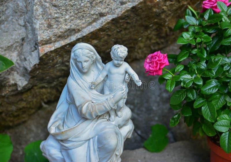 Wit steenstandbeeld van maagdelijke Mary die een baby vervoeren stock fotografie