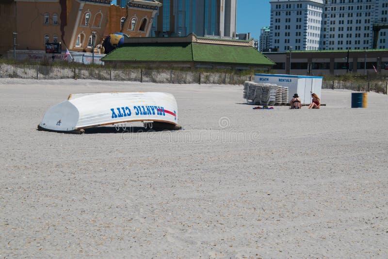 Wit strandzand met de reddingsboot gedraaide bovenkant van Atlantic City - neer Er zijn twee jonge tienermeisjes die op het zand  royalty-vrije stock afbeeldingen