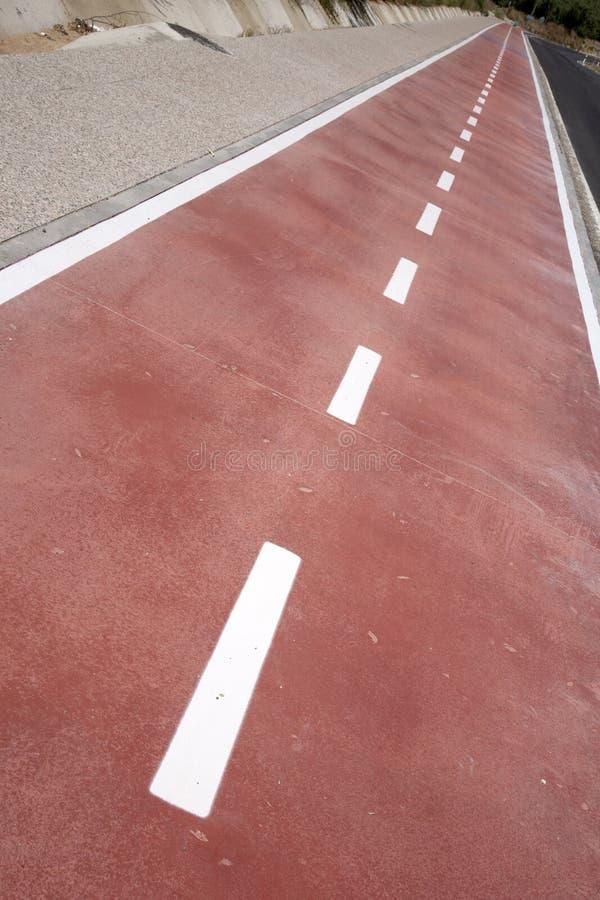 Wit teken dat van fiets en witte pijl één manier op asfaltweg richt stock fotografie