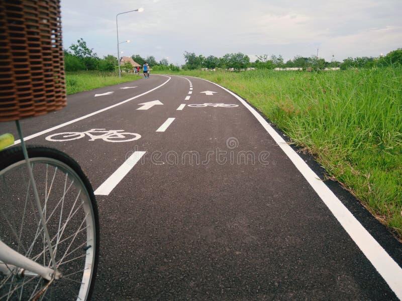 Wit teken dat van fiets en witte pijl één manier op asfaltweg richt stock foto
