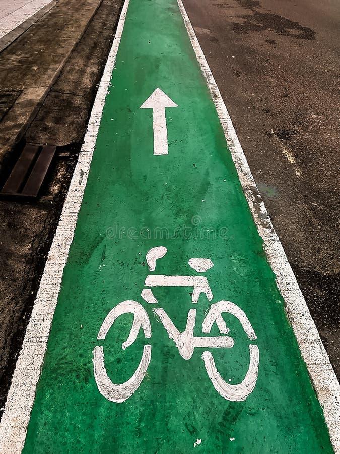 Wit teken dat van fiets en witte pijl één manier op asfaltweg richt stock foto's