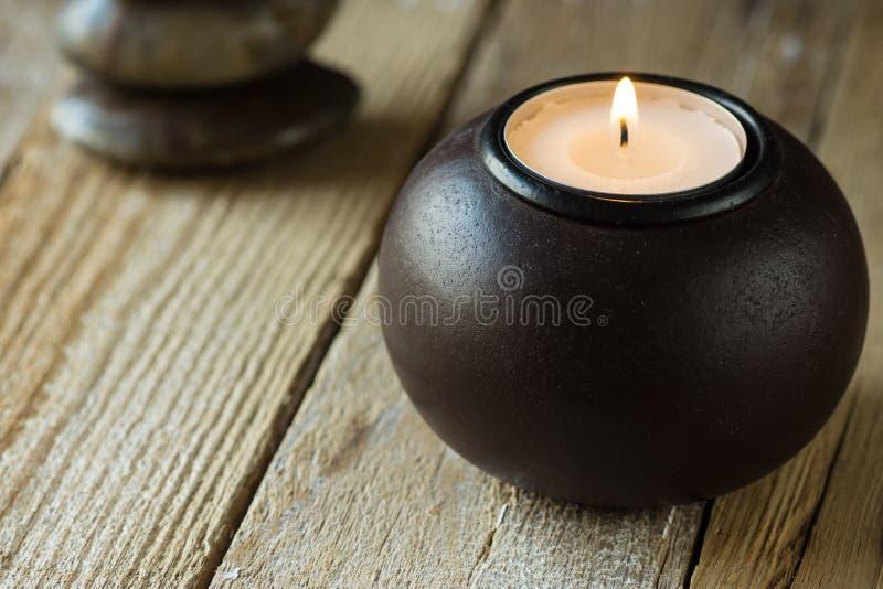 Wit theelicht in een zwarte houten kaarshouder en zen evenwichtige stenen op achtergrond, copyspace voor tekst, harmonieconcept stock fotografie