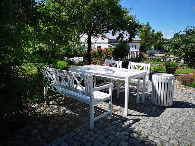 Wit tuinmeubilair in mooie tuin stock afbeelding