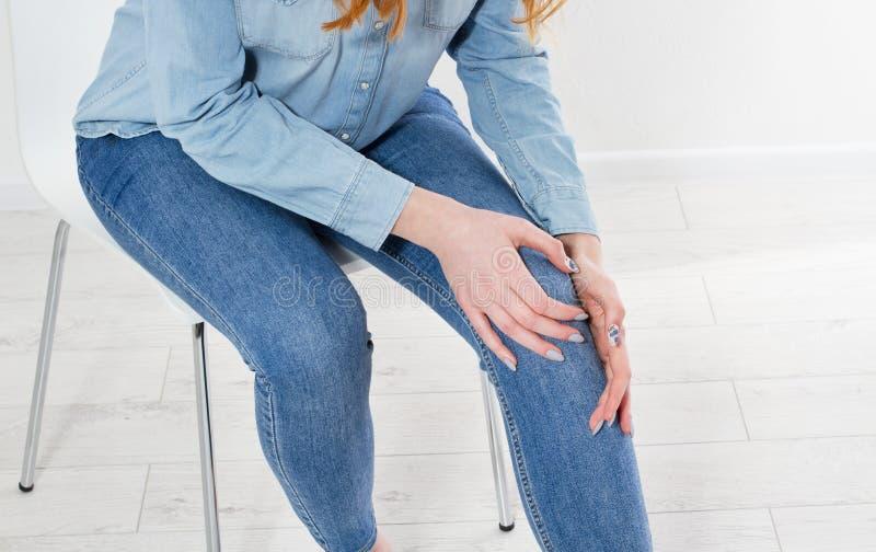 Wit van jonge vrouw die haar pijnlijke knie, Medisch en gezondheidszorgconcept masseren De ruimte van het exemplaar stock afbeeldingen