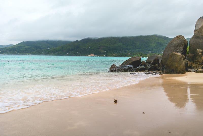 Wit zand, donkere hemel, granietstenen en turkooise overzees bij Sprookjeslandstrand, Seychellen Afrika stock fotografie