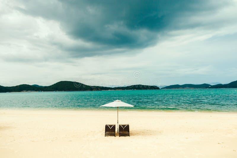 Wit zandstrand met twee sunbeds, paraplu, zonder mensen royalty-vrije stock afbeelding
