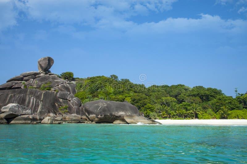 Wit zandstrand, paradijslagune Eiland in de Oceaan Zeegezicht met azuurblauw water, rots, grote stenen en tropisch bos stock afbeeldingen