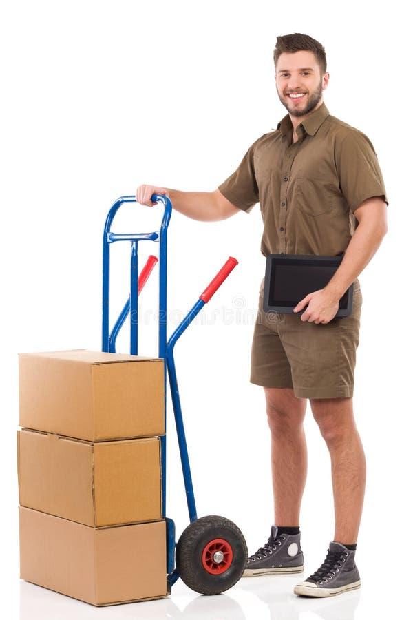 Wita de messager un comprimé numérique posant avec un chariot de poussée photo stock