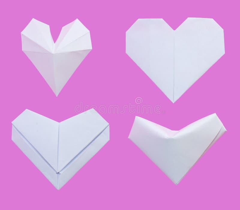 Witboek in diverse die hartvormen wordt op roze achtergrond worden geïsoleerd gevouwen die stock afbeeldingen