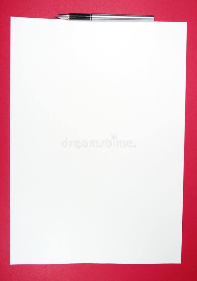 Witboek en pen op rode achtergrond royalty-vrije stock afbeeldingen