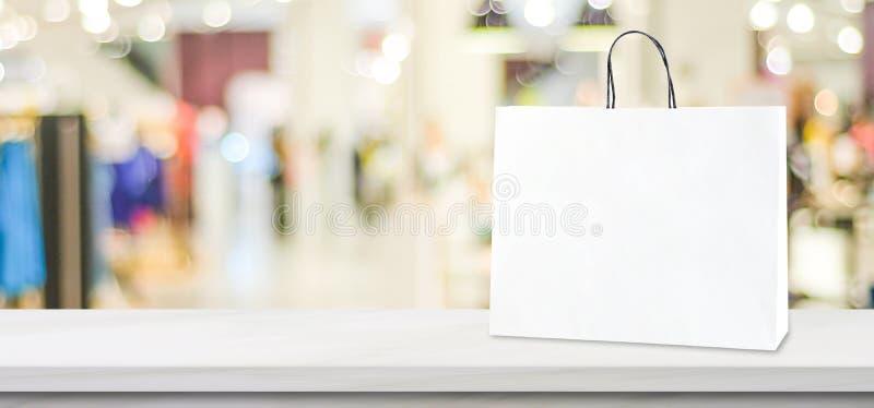 Witboek het winkelen zak die zich op witte marmeren lijst over vage opslagachtergrond bevinden met exemplaarruimte, bedrijfs mark stock fotografie