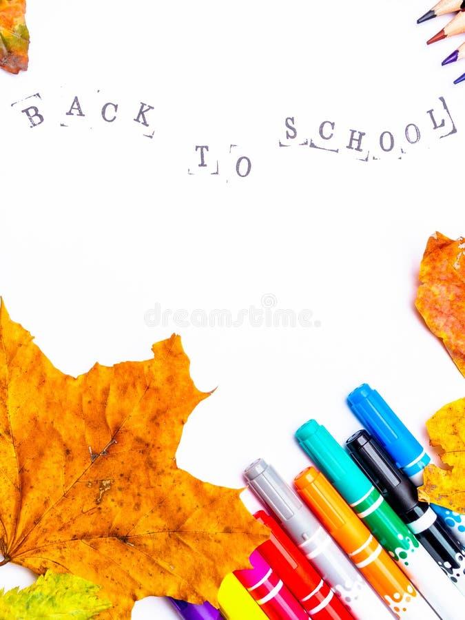 Witboek met de inschrijving terug naar school met tellers, geïsoleerde potloden stock foto's