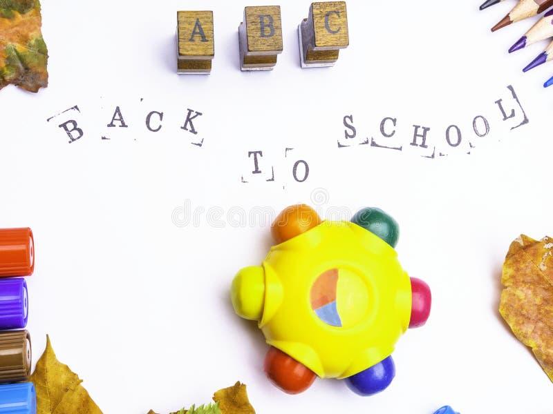 Witboek met gestempelde inschrijving terug naar school met tellers, geïsoleerde potloden stock foto