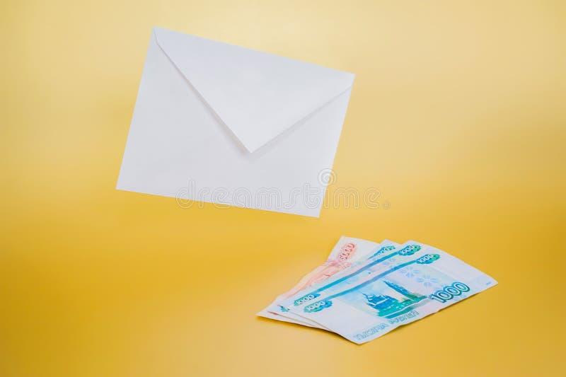 Witboekenvelop en geld op een duidelijke achtergrond stock afbeeldingen