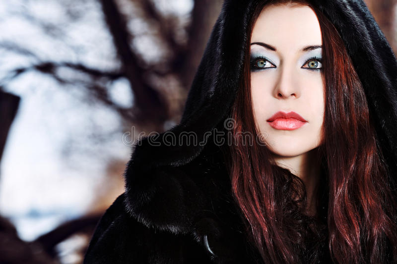 Witch. Shot of a gothic woman in a winter park. Fashion royalty free stock image