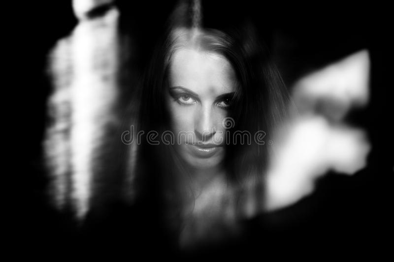 Witch. Female witch behind the dark glass with reflections stock photo
