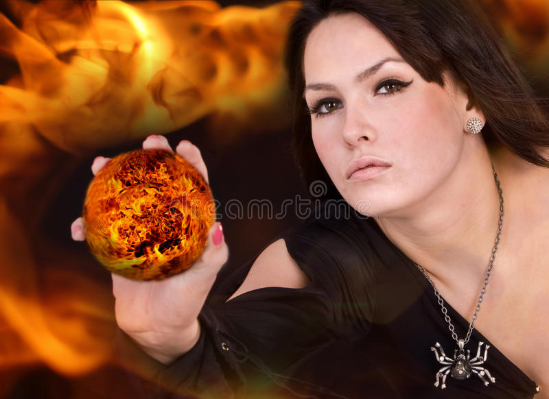 Witch in black dress with fire ball on flame. Aggressive halloween witch in black dress and spider with fire ball on flame stock image