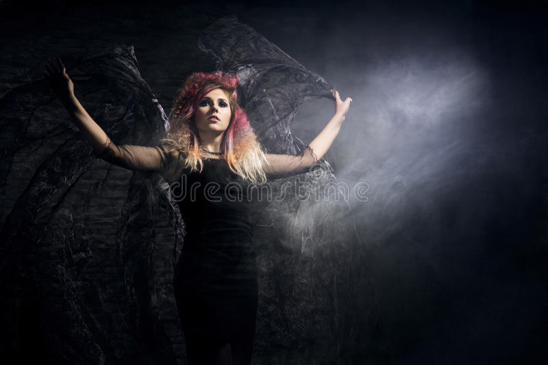 Witch in a blowing textile over the Halloween background.  stock photography