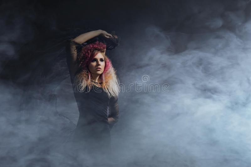 Witch in a blowing textile over the Halloween background.  royalty free stock image